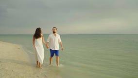 Pares novos que guardam as mãos, andando ao longo da borda da água perto do mar Grandes férias nos trópicos vídeos de arquivo