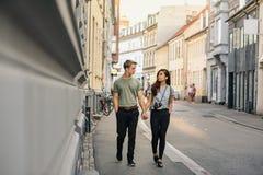 Pares novos que guardam as mãos ao andar ao longo de um passeio da cidade fotos de stock royalty free