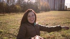 Pares novos que guardam as mãos e que circundam com um sorriso Andam através do parque vídeos de arquivo