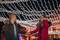 Pares novos que guardam as mãos na noite durante feriados de inverno foto de stock