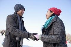 Pares novos que guardam as mãos na pista de gelo Fotos de Stock