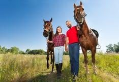 Pares novos que guardam as mãos e que andam com cavalos Fotos de Stock Royalty Free
