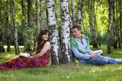 Pares novos que guardam livros no parque pelo tronco de árvore, olhando se Fotografia de Stock Royalty Free