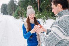 Pares novos que guardam o coração da neve nas mãos da floresta do inverno em mitenes feitos malha com coração da neve no dia de i fotos de stock