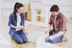 Pares novos que instalam a mobília na casa nova imagens de stock