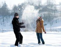 Pares novos que jogam com neve Fotografia de Stock
