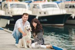 Pares novos que jogam com um cão no porto Imagens de Stock Royalty Free