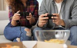 Pares novos que jogam jogos de v?deo em casa fotografia de stock royalty free