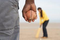 Pares novos que jogam o grilo na praia Holid do outono Foto de Stock