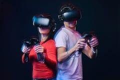 Pares novos que jogam os jogos de vídeo que vestem vidros da realidade virtual com controladores fotos de stock royalty free