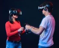 Pares novos que jogam os jogos de vídeo que vestem vidros da realidade virtual com controladores foto de stock