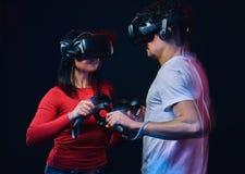 Pares novos que jogam os jogos de vídeo que vestem vidros da realidade virtual com controladores imagens de stock royalty free