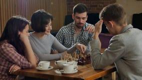 Pares novos que jogam a xadrez interna com amigos imagens de stock
