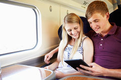 Pares novos que leem um livro na viagem de trem Imagens de Stock Royalty Free