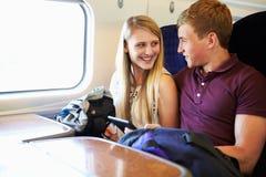 Pares novos que leem um livro na viagem de trem Fotografia de Stock Royalty Free