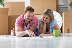 Pares novos que movem-se na casa nova, desembalando coisas e olhando a fotografia de stock