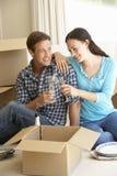 Pares novos que movem-se na casa nova que comemora com Champagne Imagem de Stock Royalty Free
