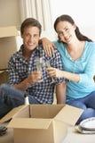 Pares novos que movem-se na casa nova que comemora com Champagne Fotos de Stock