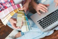Pares novos que movem-se para o lugar novo que senta-se com opinião superior do close-up do portátil e da paleta de cores imagens de stock
