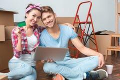 Pares novos que movem-se para o lugar novo que senta-se com o portátil que mantém o sorriso do cartão de crédito alegre imagem de stock royalty free