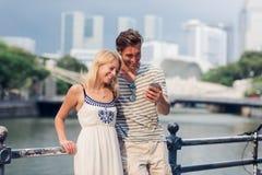 Pares novos que olham algo em um telefone ao visitar uma cidade estrangeira fotografia de stock