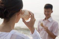 Pares novos que olham as conchas do mar, guardando o shell à orelha Foto de Stock