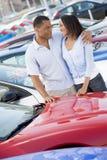 Pares novos que olham carros novos Fotografia de Stock Royalty Free