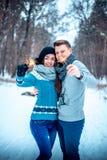 Pares novos que olham a floresta do inverno dos chuveirinhos fotografia de stock