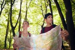 Pares novos que olham o mapa durante o passeio em a montanha Imagens de Stock Royalty Free