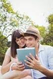 Pares novos que olham a tabuleta digital Foto de Stock Royalty Free