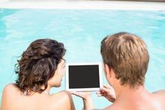 Pares novos que olham a tabuleta digital pela piscina Fotos de Stock