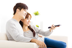 pares novos que olham a tevê na sala de visitas Fotografia de Stock Royalty Free