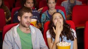 Pares novos que olham um filme Fotografia de Stock