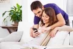 Pares novos que olham um smartphone em casa fotos de stock
