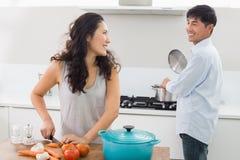 Pares novos que preparam o alimento junto na cozinha imagens de stock