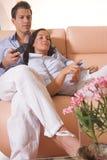 Pares novos que prestam atenção à tevê no sofá Imagens de Stock