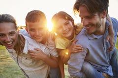 Pares novos que rebocam suas jovens crianças fora fotografia de stock royalty free