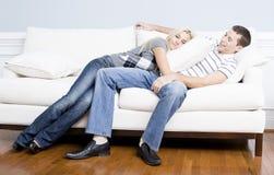 Pares novos que reclinam no sofá fotografia de stock