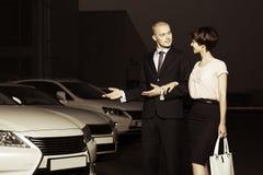 Pares novos que recolhem o carro novo no lote do negócio Imagens de Stock