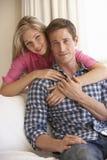 Pares novos que relaxam em Sofa Together At Home Fotos de Stock
