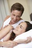 Pares novos que relaxam na cama imagem de stock royalty free