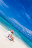 Pares novos que relaxam na praia tropical da areia no céu azul Fotografia de Stock