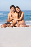 Pares novos que relaxam no Swimwear desgastando da praia Imagens de Stock