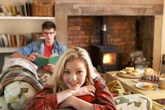 Pares novos que relaxam pelo incêndio Fotografia de Stock