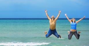 Pares novos que saltam na praia Imagem de Stock