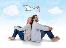 Pares novos que sentam junto o pensamento sobre seu bebê de vinda no conceito da gravidez fotos de stock