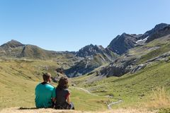 Pares novos que sentam para baixo e que olham um vale em Pyrenees fotografia de stock royalty free