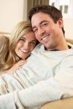 Pares novos que sentam-se e que relaxam no sofá Fotografia de Stock Royalty Free