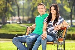 Pares novos que sentam-se em um banco no parque imagem de stock royalty free