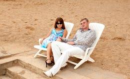 Pares novos que sentam-se em um vadio do sol Imagens de Stock Royalty Free
